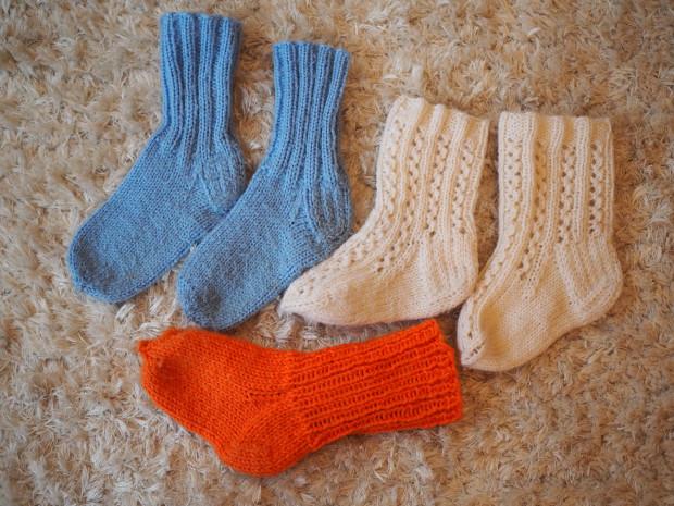 Villasukkia. Merja mummi on kutonut siniset ja oranssit. Toinen oranssi sukka oli kuvaushetkellä ulkona nukkuvan Milon jalassa. Valkoiset villasukat Amalia on saanut aikoinaan lahjaksi eräältä ihanalta lukijalta ja nyt ne pääsevät lämmittämään myös pikkuveljen varpaita <3