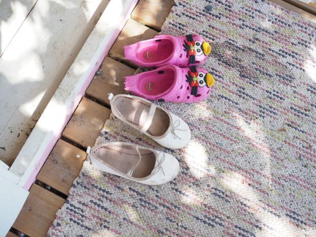 Pikkutyttöjen kengät leikkimökin terassilla