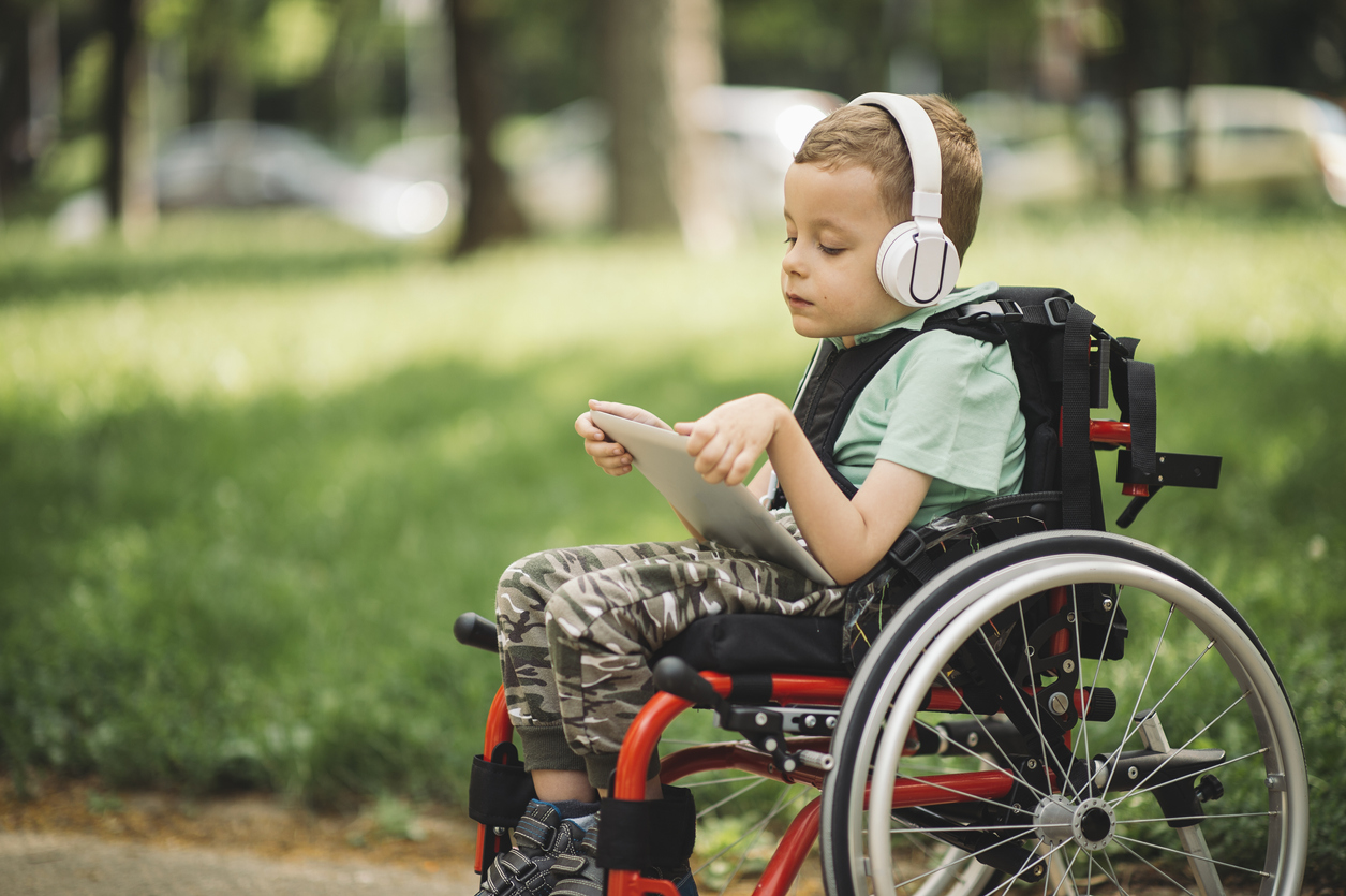 vammainen poika istuu pyörätuolissa ja kuuntelee musiikkia