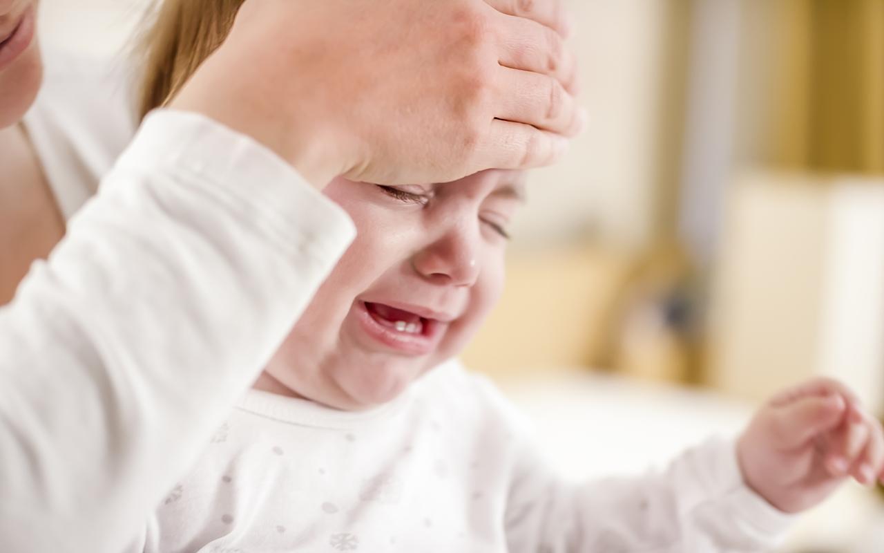 Kuumemittari: vanhempi kokeilee lapsen otsaa