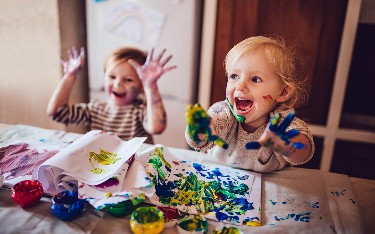 lapsilisä 2022 - Kaksi pientä lasta maalaa pöydän ääressä.