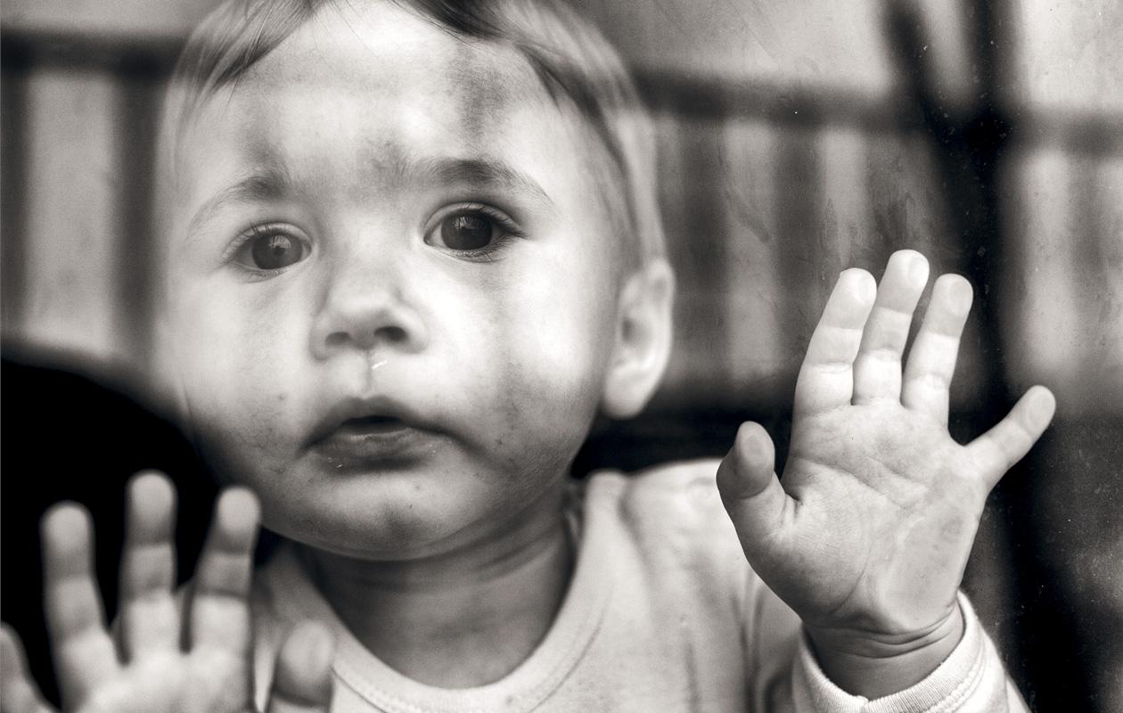 surullinen lapsi seisoo ikkunan takana