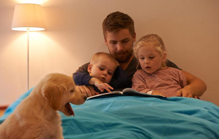 Isä lukee iltasatua sängyssä kahdelle lapselle, koira istuu etualalla.