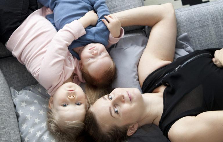 Bloggari Miia Metso sekä lapset Ruu ja Remu makoilevat sohvalla.
