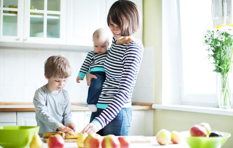 äiti ja lapsi pilkkoo hedelmiä