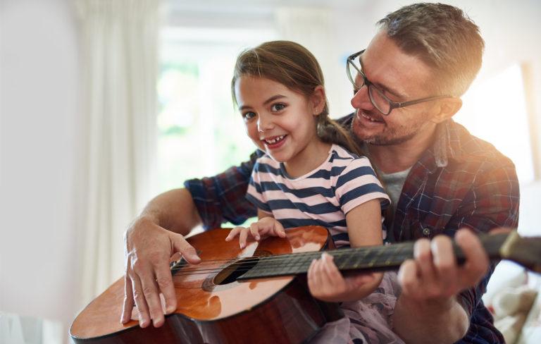 Iloinen isä ja tytär soittavat kitaraa.