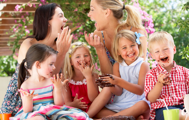 Äidit ja lapset nauravat piknikillä