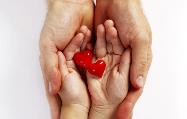isä antaa lapselle sydämiä. kädet
