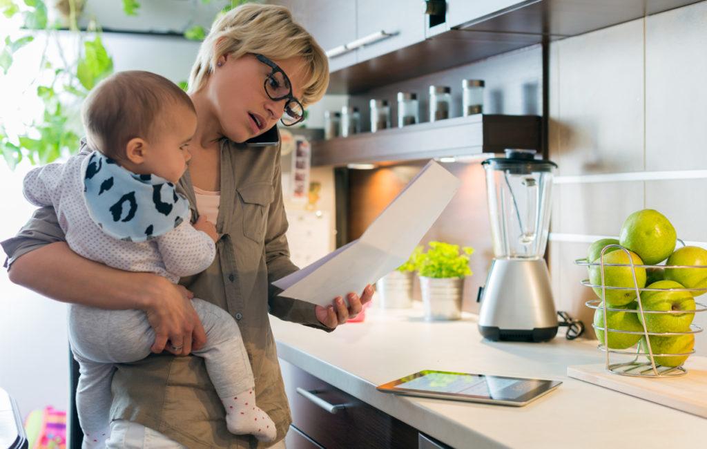Nainen katsoo papereita, puhuu puhelimeen ja pitää vauvaa sylissään keittiössä.