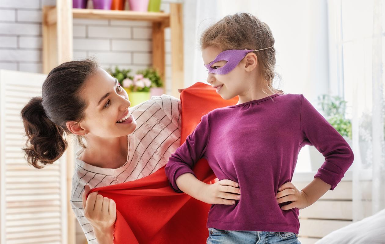 Äiti pukee supersankarin viittaa tyttärelleen.