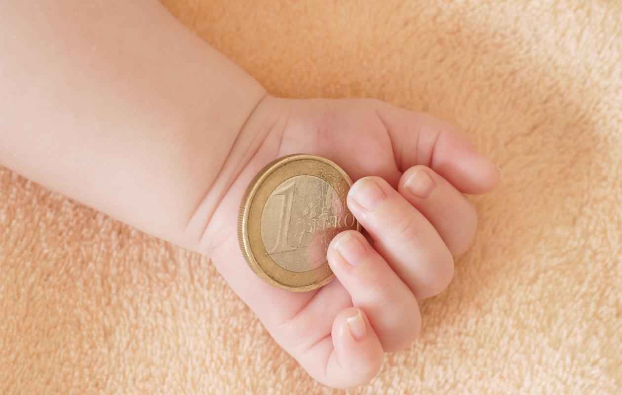 Vauva pitää euron kolikkoa kädessään. Äitiysvapaa, äitiysraha.