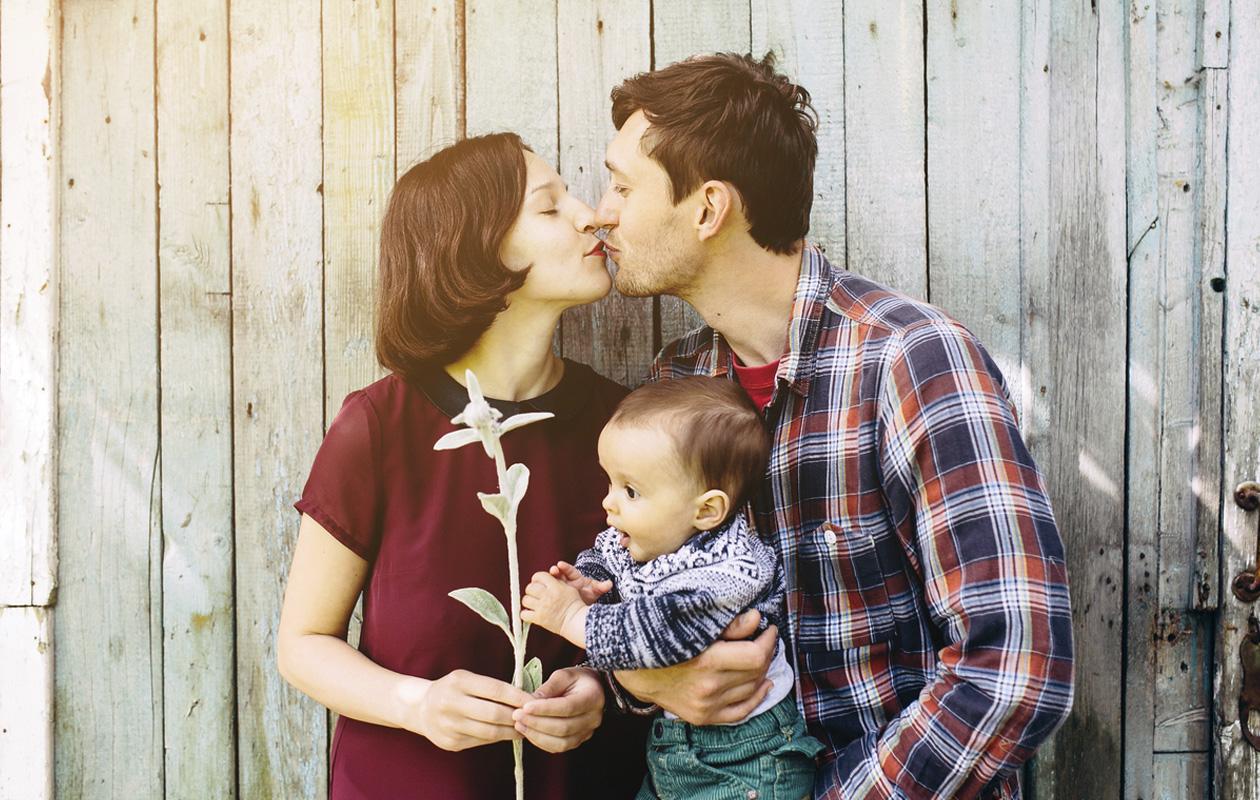 nuori pariskunta suutelee ja miehellä on lapsi sylissä