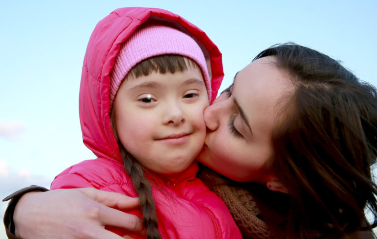 äiti pussaa lasta poskelle, jolla on down syndrooma
