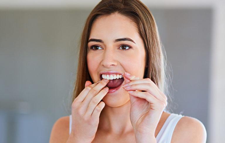 Nainen puhdistaa hammaslangalla hampaita