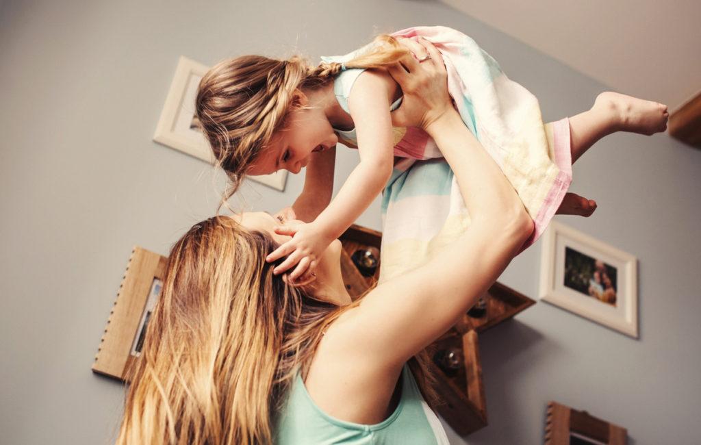 iloinen äiti ja lapsi leikkivät yhdessä