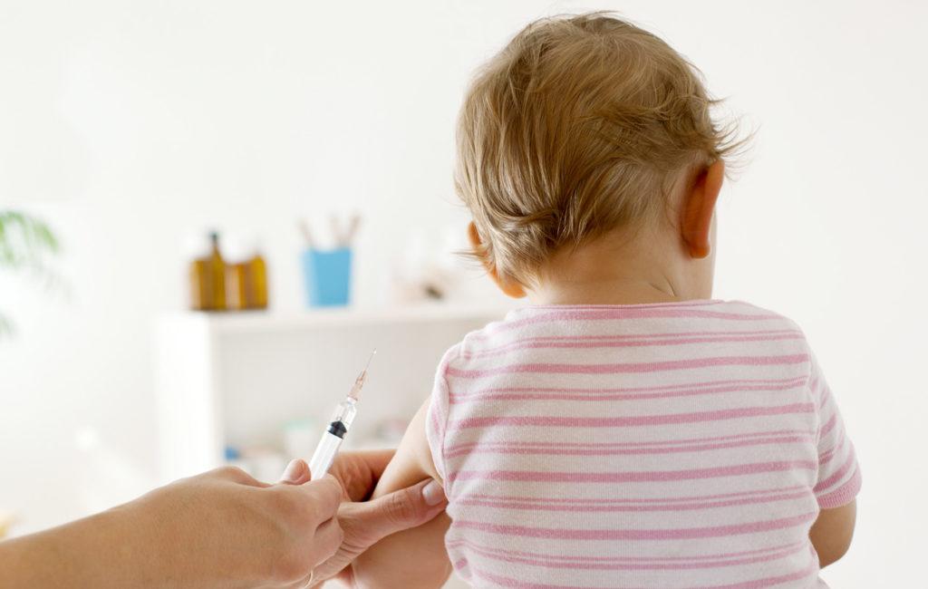 Pieni lapsi istuu selin ja häntä rokotetaan