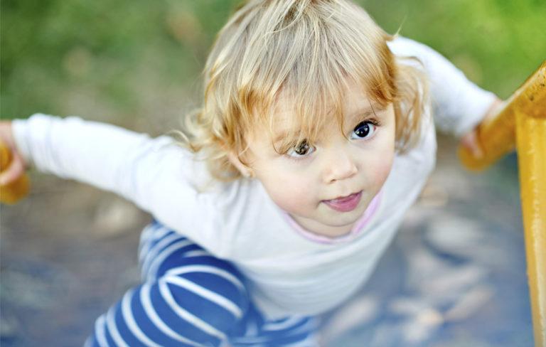 Pieni tyttö kiipeää kiipeilytelineessä ylöspäin