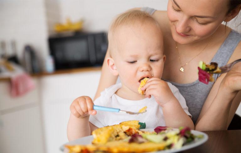 Lapsi syö ruokaa äidin sylissä.