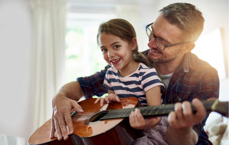 pikkutyttö istuu kummisedän sylissä ja opettelee kitaran soittoa