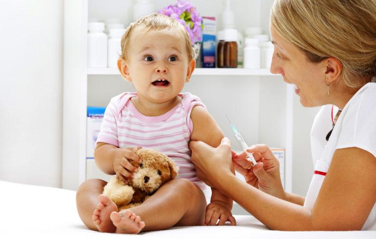 hoitaja rokottaa taaperoa