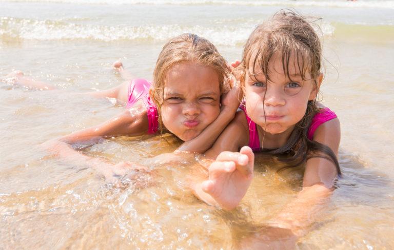 kaksi tyttöä uimassa ranta aurinko