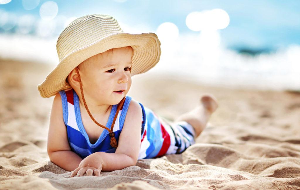 Pieni lapsi voi nauttia auringosta turvallisesti, kun hänet suojaa säteilyltä oikeanlaisin vaattein ja voitein