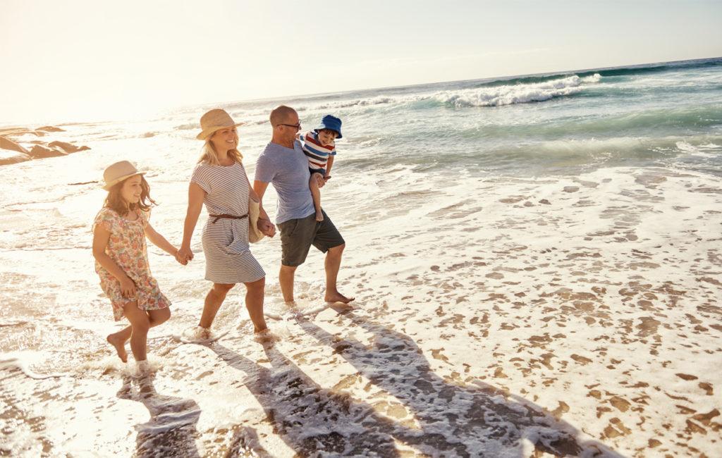 Äiti, isä, tytär ja poika kävelemässä meren rannalla