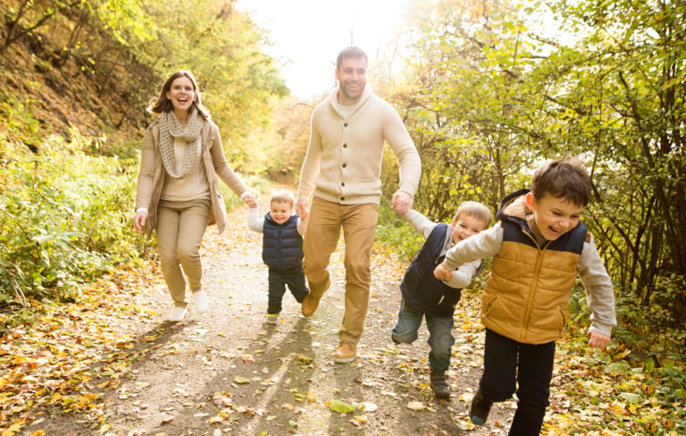 Äiti, isä ja kolme lasta kävelyllä metsässä