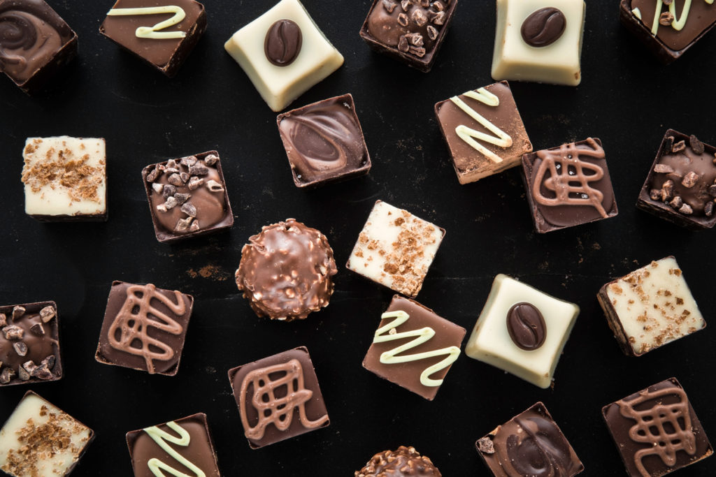 Delicious chocolate candies, truffles on the black background.