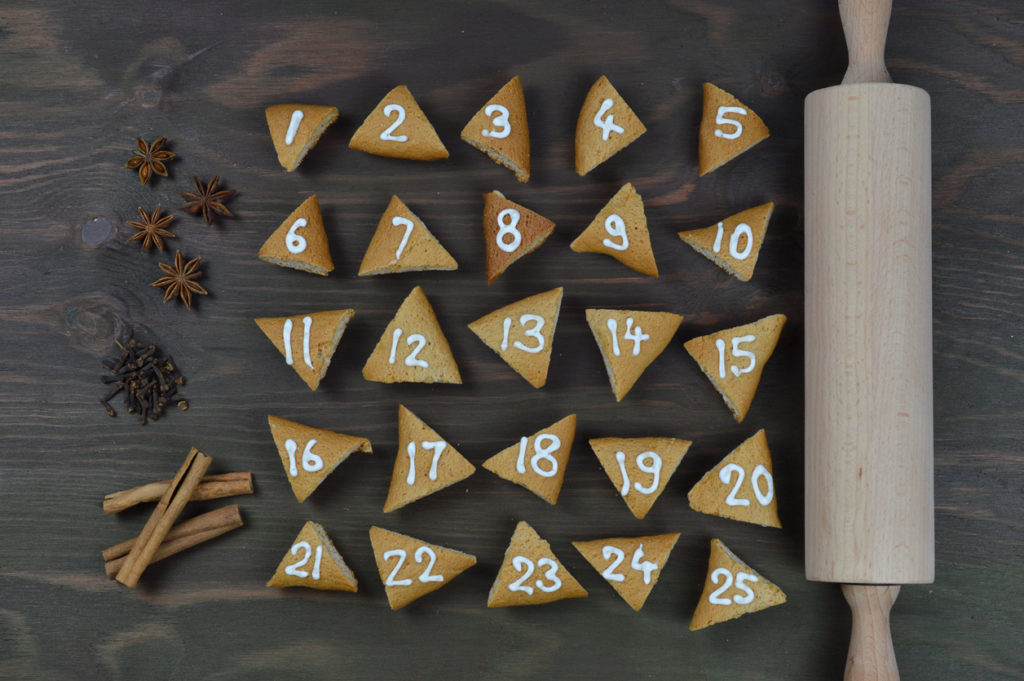 25 advent cookies on brown wood with rolling pin and spices