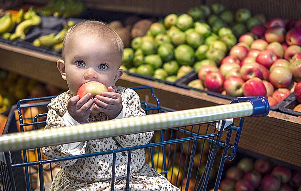 Lapsi kaupassa omena suussaan.