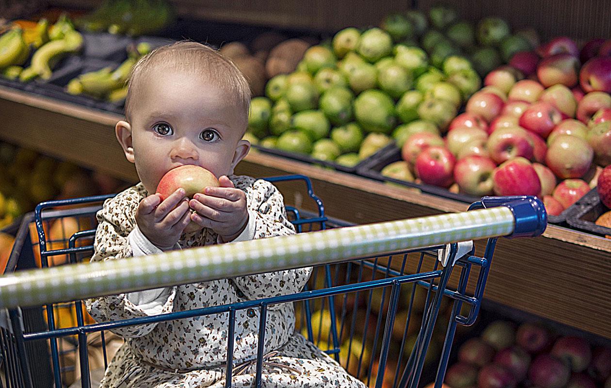 Lapsi ruokakaupassa omena suussaan.