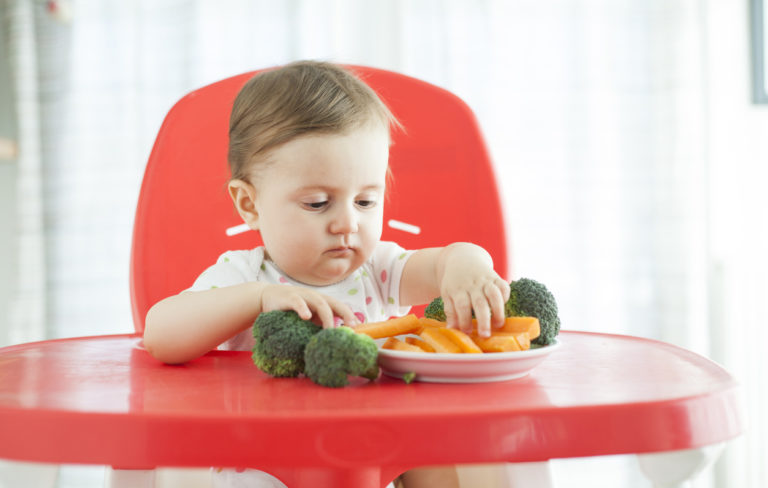 Taapero syömässä vihanneksia.