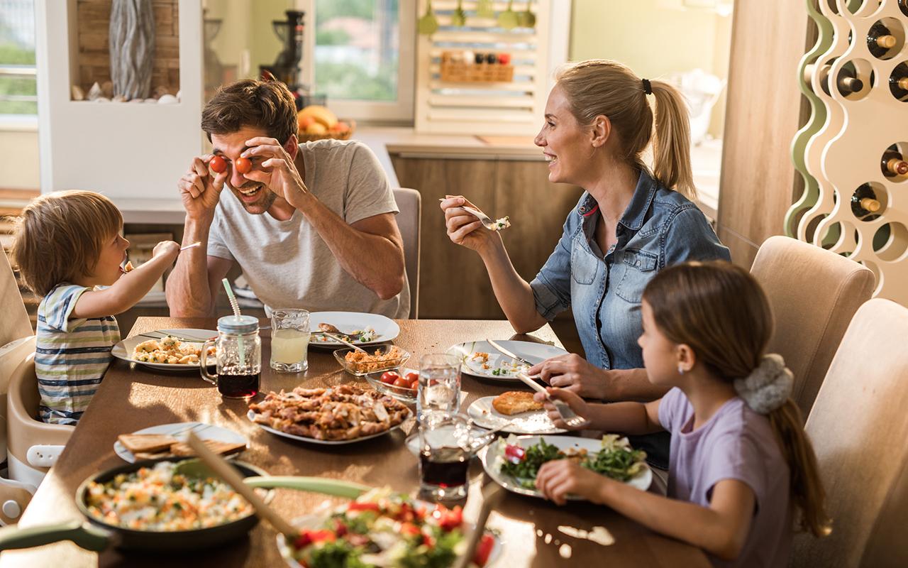 Perhe istuu pöydässä syömässä. Mies ei syö kasviksia vaan pelleilee kirsikkatomaateilla.