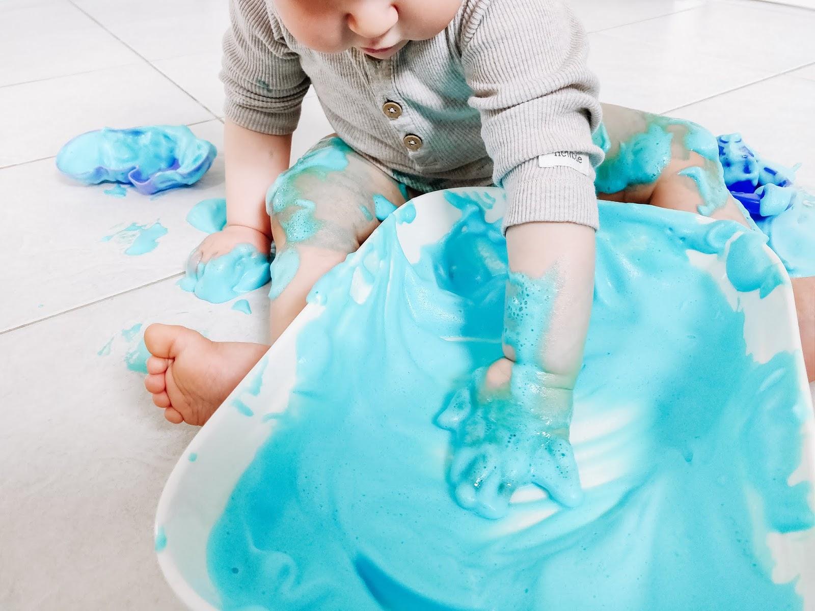 Vauva leikkii turkoosilla vaahdolla kylpyhuoneessa. Vaahtoleikki on takuuvarmaa puuhaa lapsille.