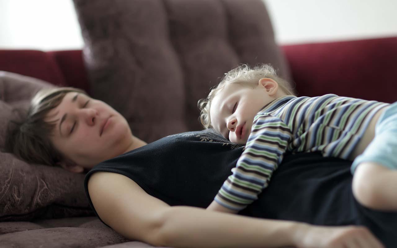 Äiti lepää sohvalla lapsi sylissään. Uupuneena saattaa olla alttiimpi tuntemukselle, että on epäonnistunut äiti.