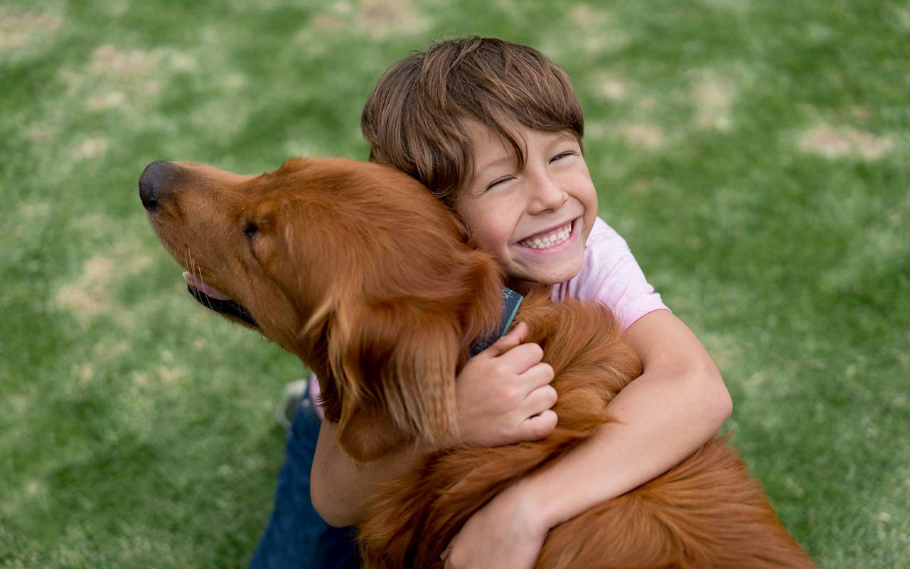 Poika halaa hymyillen koiraansa. Jokunen rakkaus-aforismi saattaa myös syntyä karvaisen kaverin innoittamana.