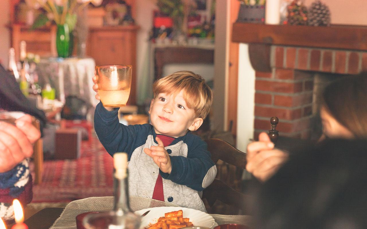Alkoholiton olut lapselle? Lapselle sopii mahdollisesti paremmin mehu. Seurueessa, jossa on mukana lapsia, tulee aikuisten käyttää alkoholia maltillisesti. Kuvassa pieni poika pitelee juhlajuomaanssa.