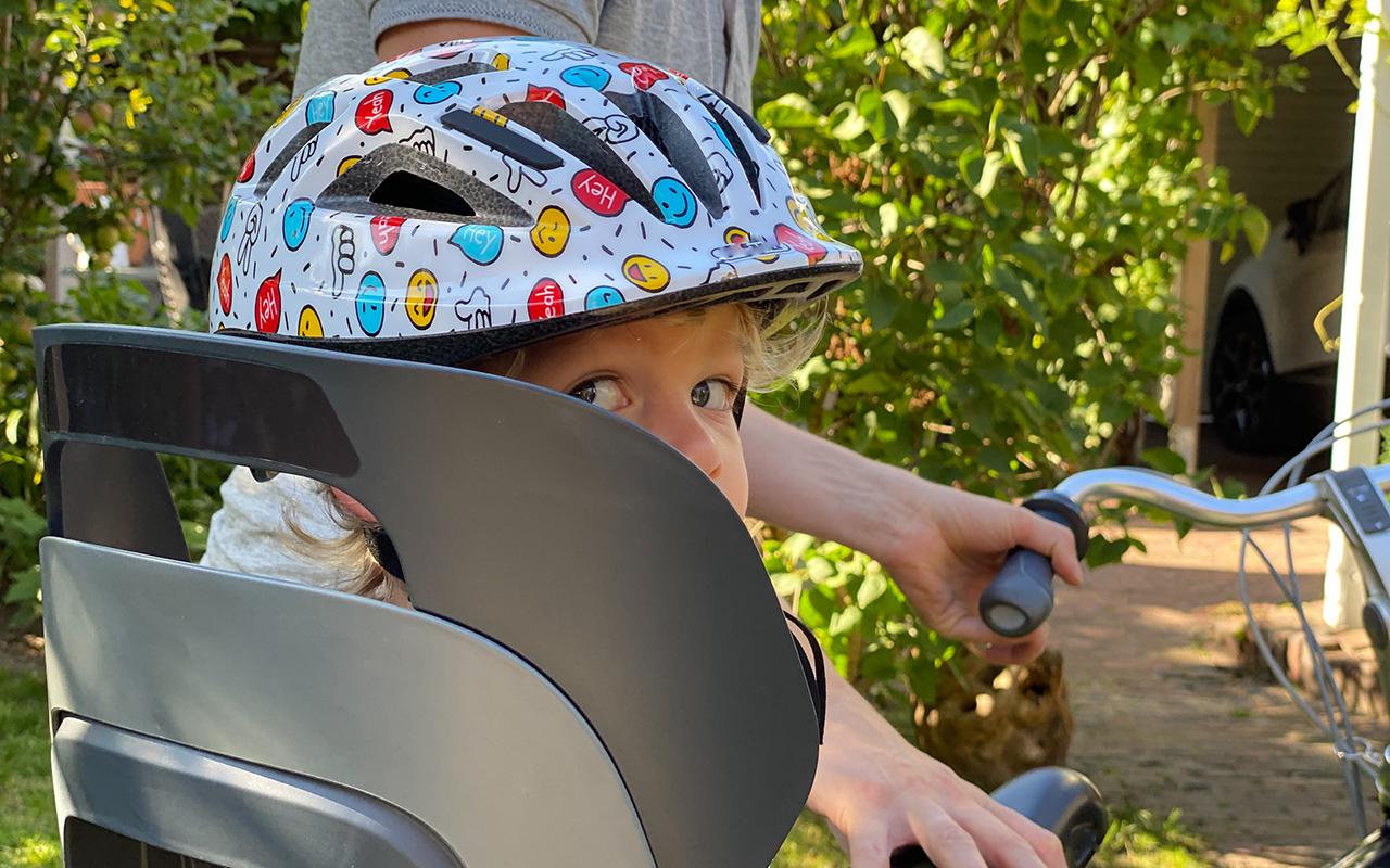 Pyöräilykypärä lapselle on tärkeä hankinta, ja sen istuvuuteen kannattaa panostaa. Kuvassa lapsi pyöränistuimessa kypärä päässä.