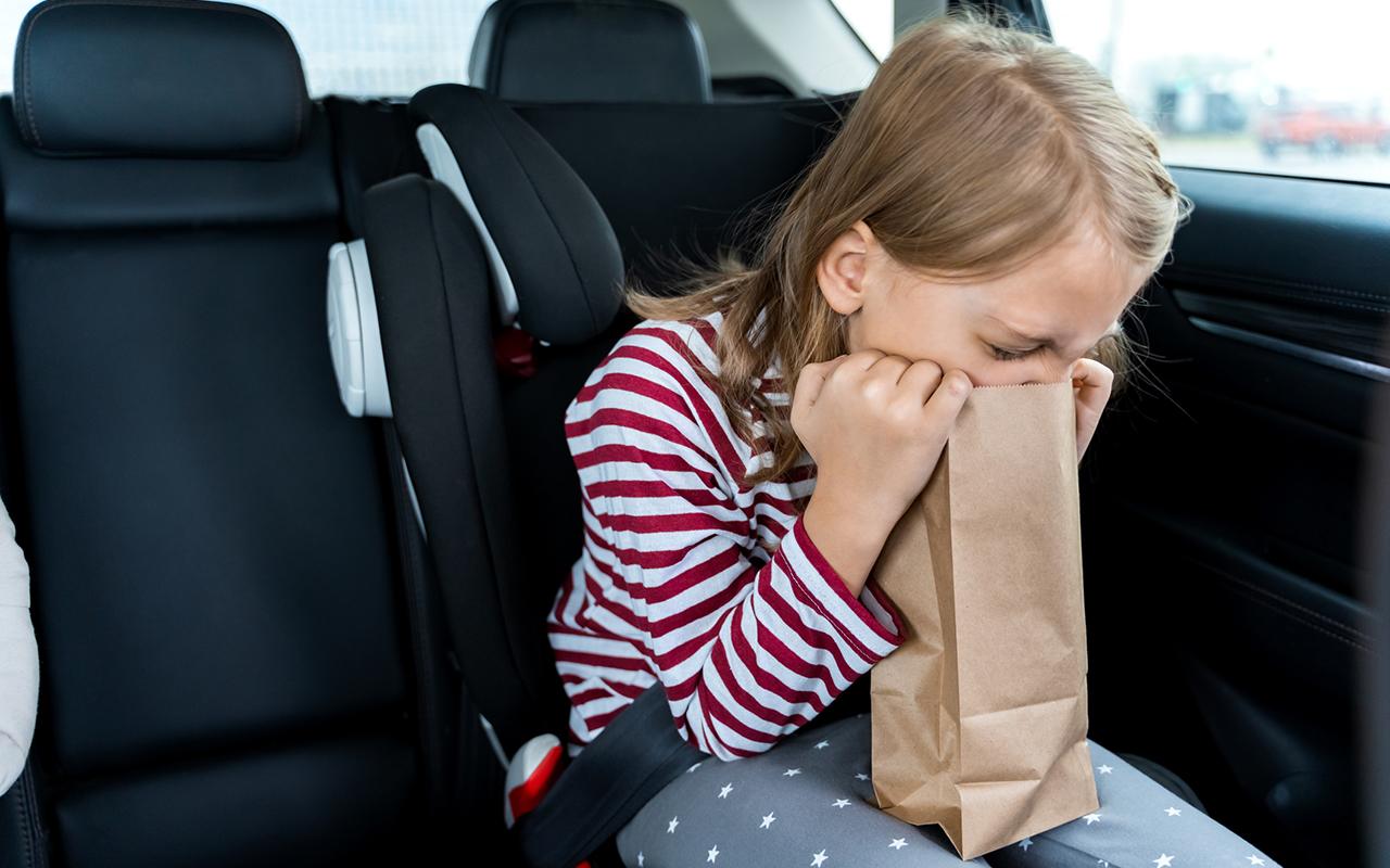 Lapsi istuu turvavyöistuimessa ja oksentaa.