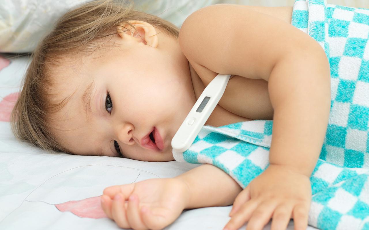 kuumemittari: lapsella on digimittari kainalossa