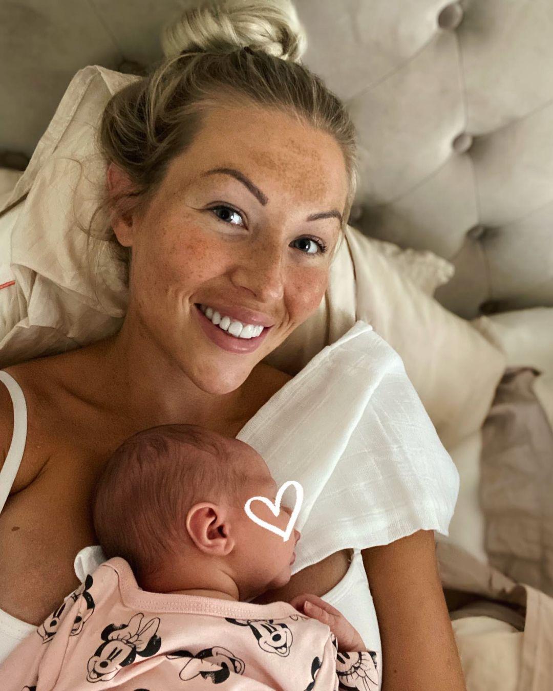 Maisa Torppa makoilee vauva rinnallaan.