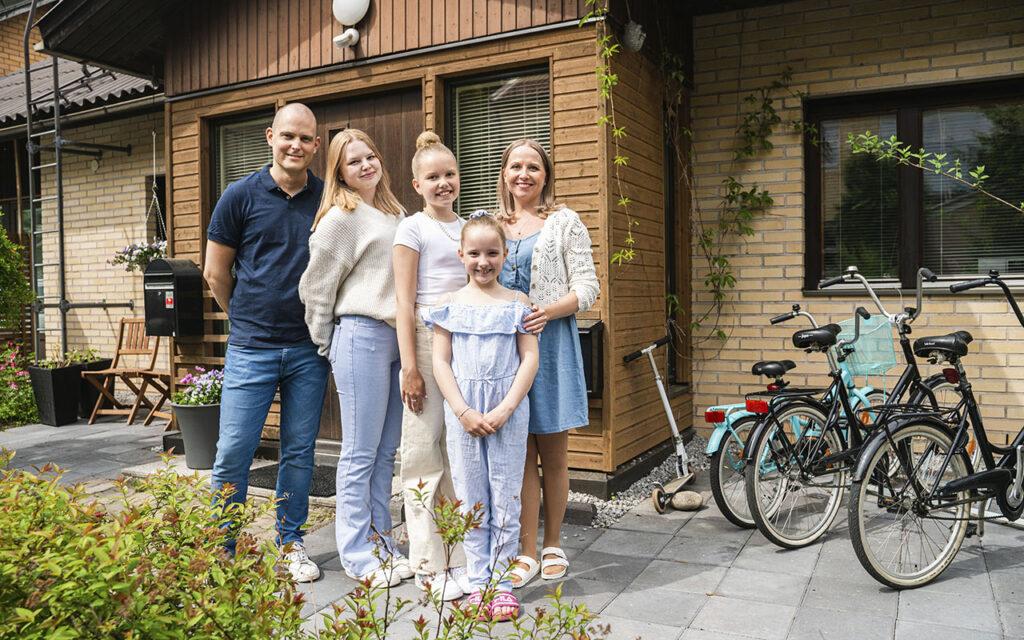 Remppa vai muutto -ohjelmassa kisaava Anna-Marian ja Tuomaksen perhe seisoo talonsa edustalla.