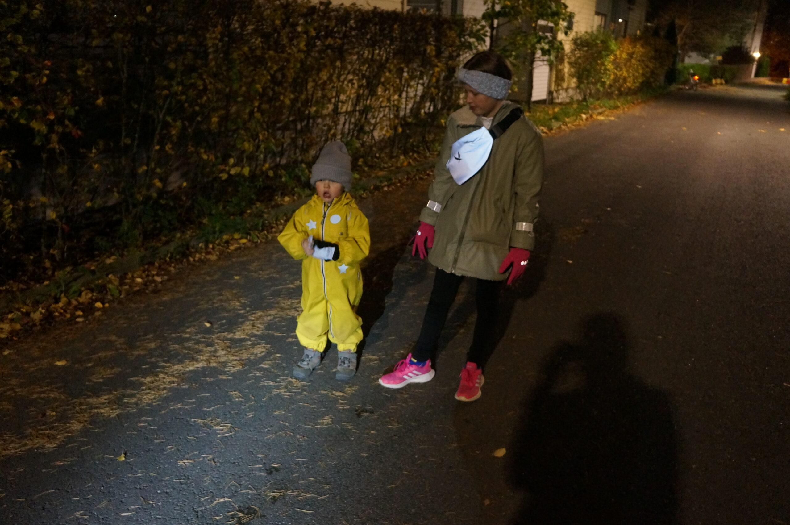 Heijastinliivi vai -vyölaukku? Kuvassa lapset pimessä heijastimet yllään.
