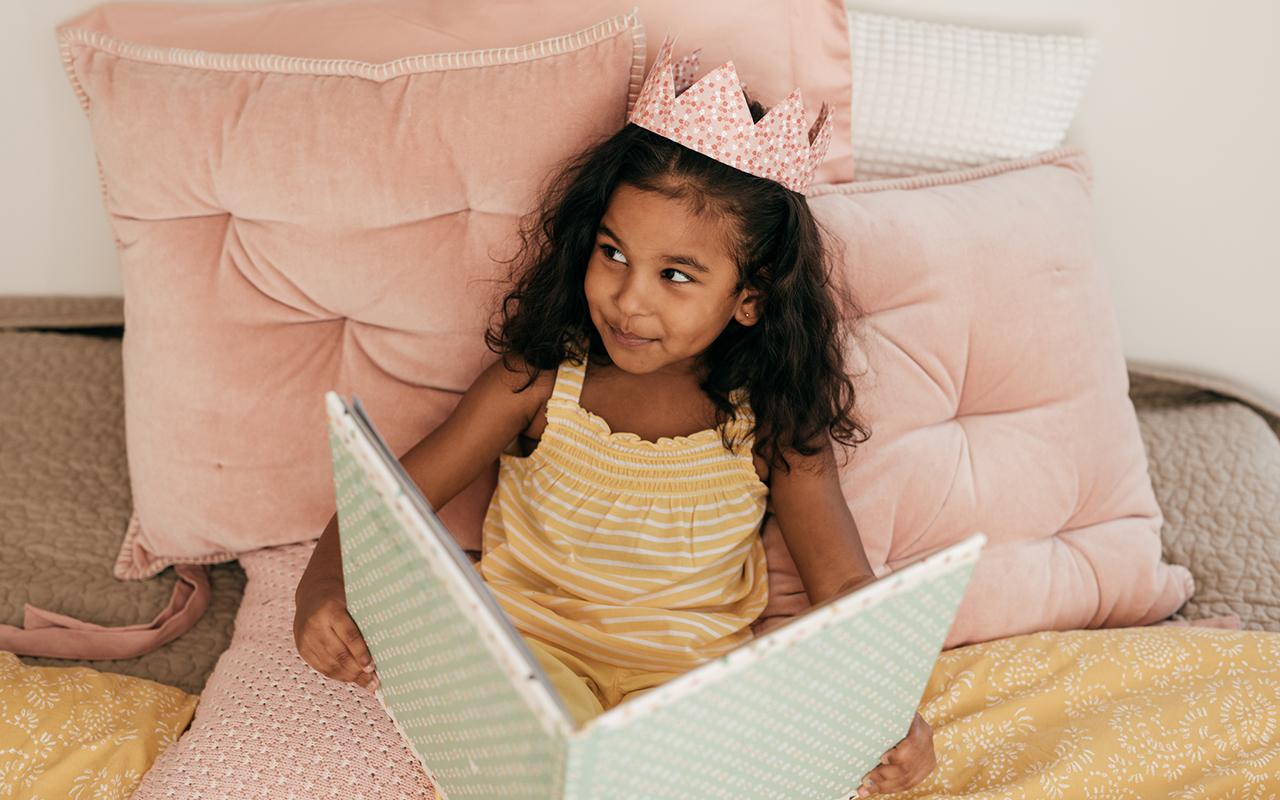 Prinsessasatu - tyttö lukee kirjaa kruunu päässään.